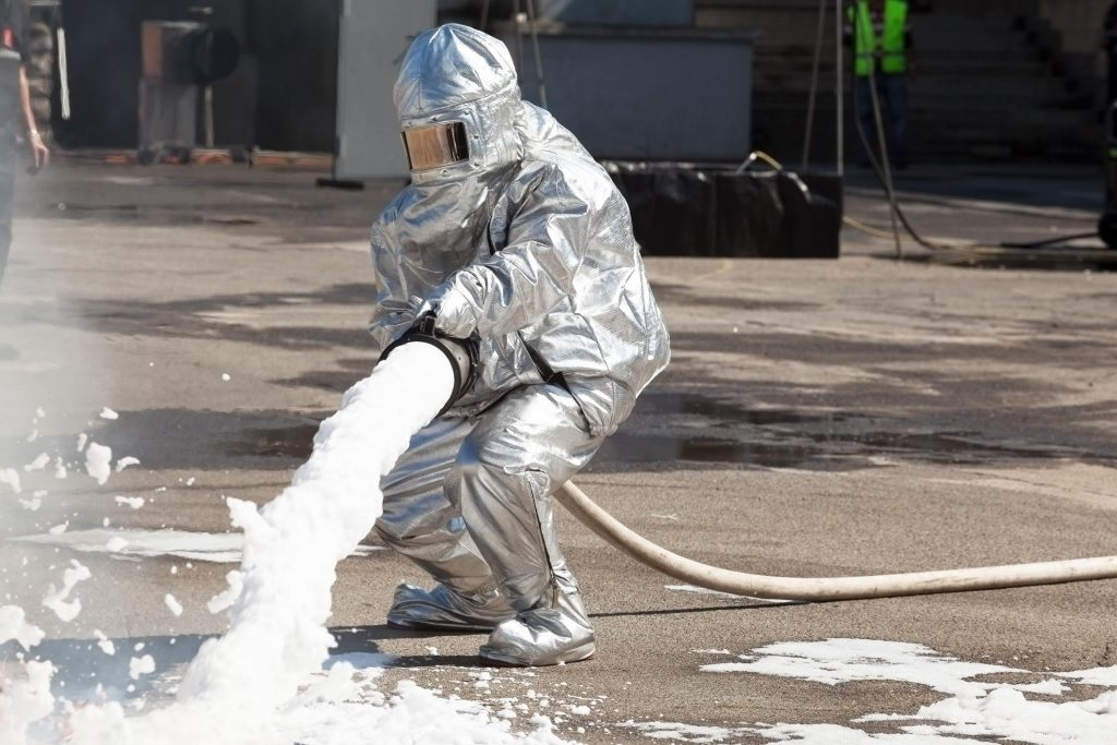 someone wearing fully equip gear spraying insulation foam