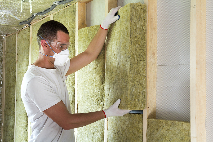 worker in protective goggles and respirator insulating rock wool insulation in wooden frame for future house walls for cold barrier.