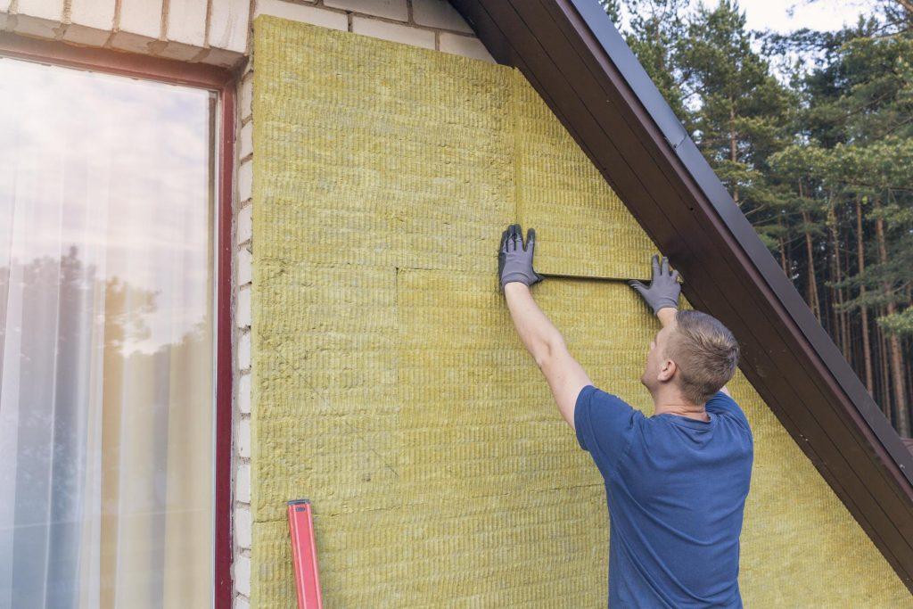 male worker installing fiber glass insulation