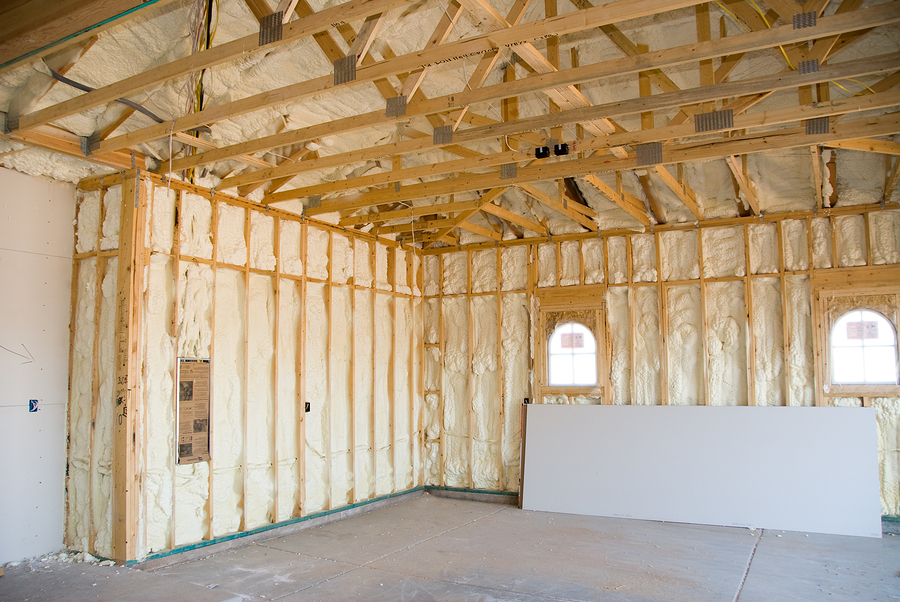 room at a newly constructed home is sprayed with liquid insulating foam before the drywall is added. Ideal for new home construction advertising and other home construction promotional inferences.
